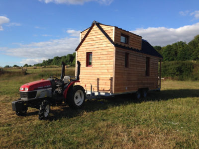 tracteur tractant une tiny house (chalet nomade)