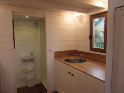 Ce chalet nomade fabriqué en Eure et Loir pour 4 personnes est équipé d'une cuisine avec un second plan de travail intégrant un évier en inox et de deux grands placards