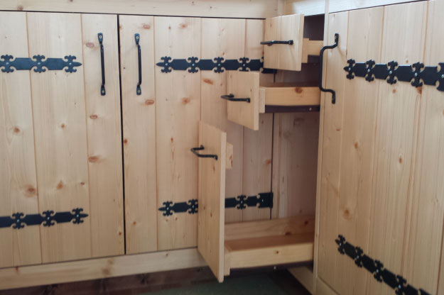 Aménagement de la cuisine avec des placards et des tiroirs coulissant afin d'optimiser l'espace de cette tiny house
