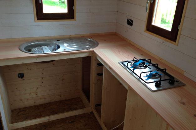 Installation de l'évier en inox et de plaques de cuisson au gaz dans la cuisine de cette mirco maison