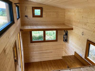 Ce modèle de tiny house créé en Eure et Loir pour 4 personnes possède 2 mezzanines accessible via un esclier optimisé et une échelle de meunier