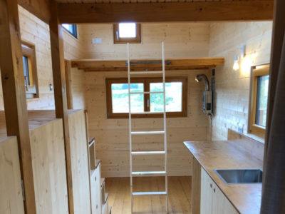 Accès à la premiere mezzanine via une échelle de meunier dans cette tiny house 100% autonome pour 4 personnes construite dans l'Orne entre Chartres, Le Mans et Alençon