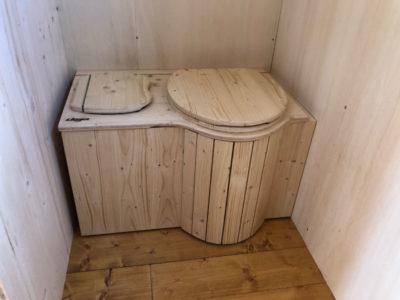 Toilettes sèches (=WC écologique) dans la salle d'eau de la Tiny House ac un rangement pour les copeaux de bois. Cette salle d'eau possède aussi un lavabo, des rangements et une douche 80x80. Toutes nos tiny houses peuvent être livrées en Bretagne: Rennes, Quimper, Nantes, Saint Brieuc, etc.