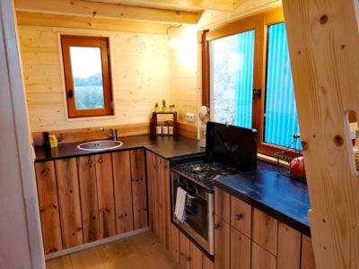 Le plan de travail en angle dans la cuisine de cette tiny house permet d'accueillir un évier en inox, des plaques de cuisson et un four encastrable. Livraison possible en Eure et Loir : Chartres, Le mans, Alençon, etc.