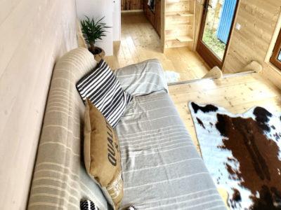 La plateforme de cette tiny house surélevant le salon dissimule les batteries pour les panneaux solaires et le récupérateur d'eaux de pluie, créée près de Chartres, du Mans, Alençon