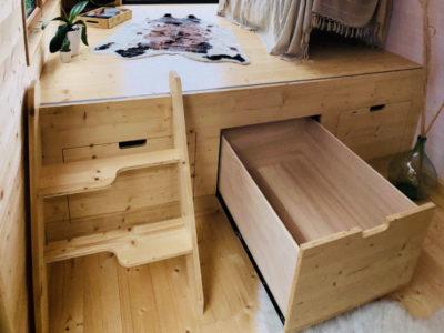 Le plancher du salon de cette tiny house surélevé intègre des tiroirs coulissants, créée près de Chartres, du Mans et d'Alençon