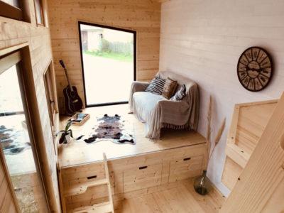 Le salon de cette tiny house surélevé dissimule des batteries pour les panneaux solaires et le récupérateur d'eaux de pluie, créée près de Chartres, du Mans et d'Alençon