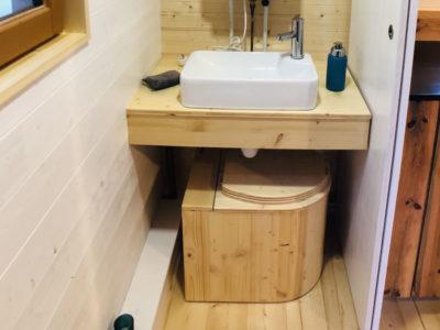 Toilettes sèches mobiles (=WC écologique) dans la salle d'eau de la Tiny House à ranger sous le lavabo.
