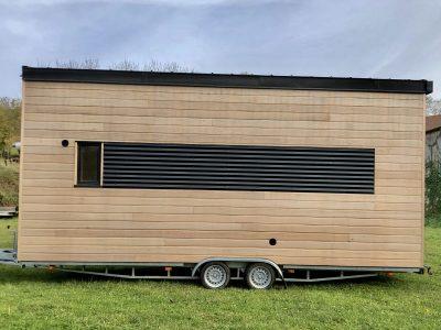 Vue extérieure avec intégration d'une claire-voie, d'une VMC et d'une gouttière pour récupérer l'eau de pluie de ce modèle de tiny house