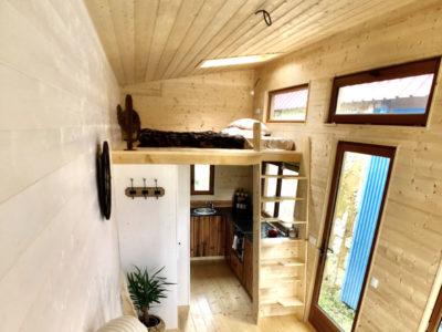 Mezzanine accessible via un escalier dit à pas japonnais avec des poignées intégrées dans ce modèle de tiny house pour 2 personnes créé près de Chartres, Le Mans et Alençon