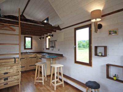 Le plan de travail en angle arrondi dans la cuisine de cette tiny house permet d'accueillir des placards en dessous. Un évier en inox est encastré au plan de travail. Livraison possible en Eure et Loir : Chartres, Le mans, Alençon, etc