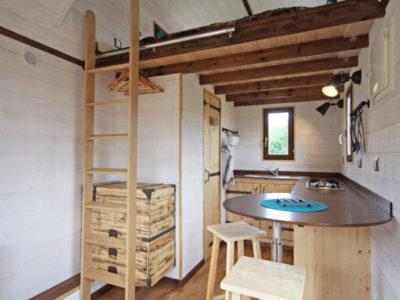 Le plan de travail en angle arrondi dans la cuisine de cette tiny house permet d'accueillir des placards en dessous. Un évier en inox est encastré au plan de travail ainsi que des plaques de cuisson. Livraison possible en Eure et Loir : Chartres, Le mans, Alençon, etc