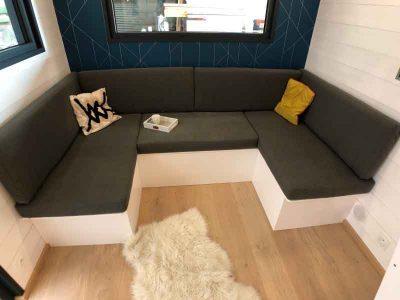 Fabrication d'un canapé sur-mesure et convertible pour 2 personnes dans le salon de ce modèle de tiny house sur-mesure La Familiale fabriquée dans le Perche en Orne entre Alençon, Le Mans en Sarthe et Chartres en Eure et Loir