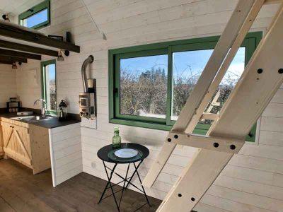 Espace cuisine avec un évier, placards et espace repas de cette tiny house sur-mesure Harmonie pour 2 personnes fabriquée dans le Perche en Orne entre Alençon, Le Mans en Sarthe et Chartres en Eure et Loir